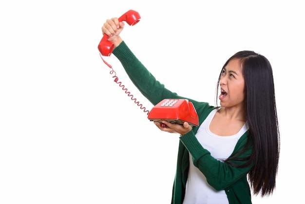 Foto de estúdio de uma jovem adolescente asiática segurando um telefone antigo