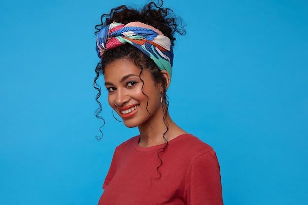 Foto de estúdio de uma jovem adorável de olhos castanhos, cacheada, vestida com uma camiseta bordô e uma faixa colorida, olhando alegremente para a frente com um sorriso encantador, isolada sobre uma parede azul