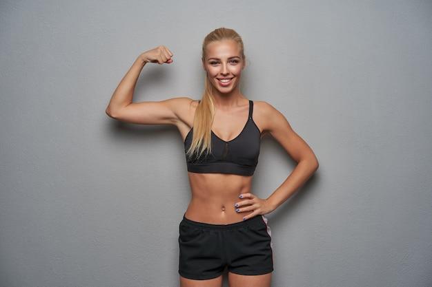 Foto de estúdio de uma jovem atraente mulher esportiva com longos cabelos loiros, sorrindo alegremente para a câmera enquanto demonstra seus fortes bíceps, em pé sobre um fundo cinza claro em roupas esportivas