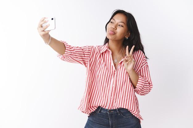 Foto de estúdio de uma jovem bonita, confiante, elegante e extrovertida, em uma blusa listrada, imitando e fazendo caretas para a câmera enquanto tira uma selfie com smartphone, mostrando o símbolo da paz