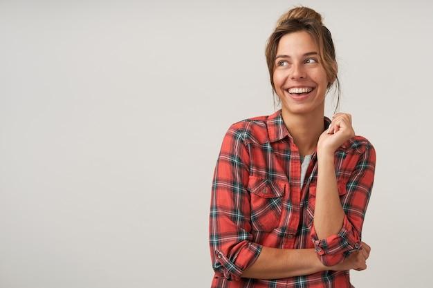 Foto de estúdio de uma jovem bonita de cabelos castanhos com penteado casual, mantendo a mão levantada, olhando alegremente para o lado com um sorriso encantador, isolada sobre fundo branco