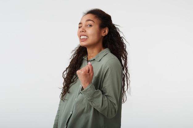 Foto de estúdio de uma jovem bonita morena de cabelos compridos morena com penteado casual, levantando o punho e mantendo um olho fechado enquanto olha para a câmera, isolada sobre fundo branco