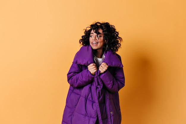 Foto de estúdio de uma jovem com uma jaqueta roxa