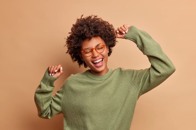 Foto de estúdio de uma jovem dançando despreocupada, se divertindo, levantando os braços e relaxando, usando óculos transparentes e um macacão casul isolado na parede marrom