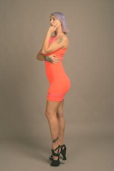 Foto de estúdio de uma jovem e bela mulher rebelde com cabelos coloridos, usando um vestido vermelho neon em cinza