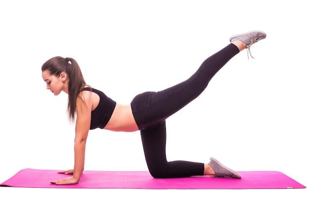 Foto de estúdio de uma jovem em forma fazendo exercícios de ioga isolados no fundo branco