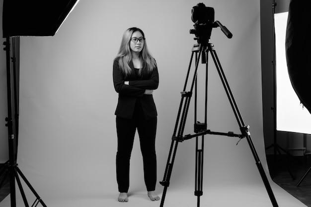 Foto de estúdio de uma jovem empresária asiática contra uma parede cinza em preto e branco