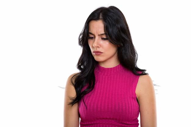 Foto de estúdio de uma jovem espanhola triste pensando enquanto olha para baixo