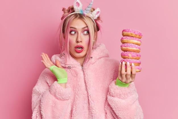 Foto de estúdio de uma jovem europeia chocada a olhar surpreendentemente para uma pilha de donuts e perceber a quantidade de calorias que contém
