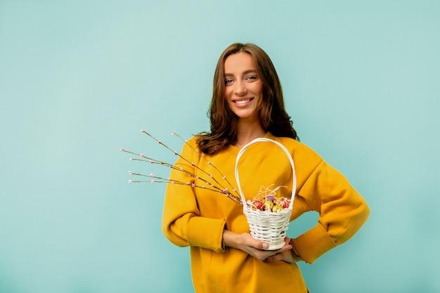 Foto de estúdio de uma jovem europeia com penteado de camisa e roupas brilhantes, posando com a cesta de páscoa do feriado, posando sobre a parede azul