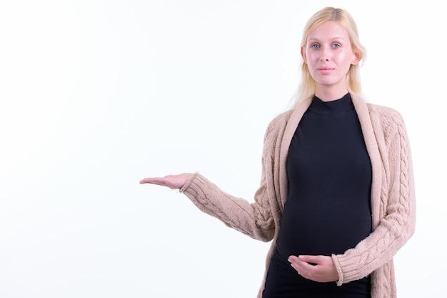 Foto de estúdio de uma jovem grávida bonita com cabelo loiro isolado contra um fundo branco