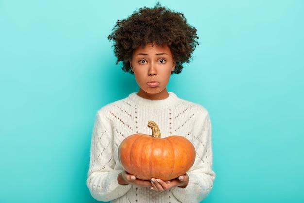 Foto de estúdio de uma jovem intrigada descontente com um penteado afro, segura uma abóbora, usa um suéter de malha branco e olha tristemente para a câmera