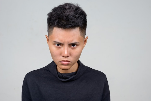 Foto de estúdio de uma jovem lésbica asiática com cabelo curto contra um fundo branco