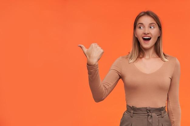 Foto de estúdio de uma jovem loira agitada, de cabelos curtos, vestida com uma blusa bege, mantendo a boca aberta enquanto dedilha para o lado, em pé sobre uma parede laranja