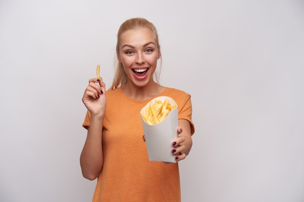 Foto de estúdio de uma jovem loira atraente feliz, regozijando-se com as batatas fritas frescas em sua mão e olhando alegremente para a câmera com um largo sorriso, posando contra um fundo branco