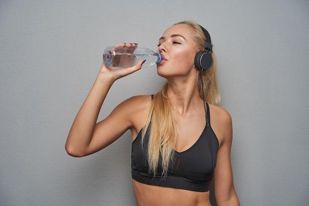 Foto de estúdio de uma jovem loira de cabelos compridos com penteado de rabo de cavalo, beber água após o treino e ouvir música com fones de ouvido, posando sobre um fundo cinza claro em top preto esportivo
