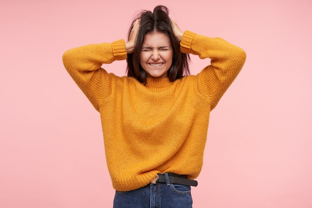 Foto de estúdio de uma jovem morena com cabelo solto, mantendo os olhos fechados e rosto carrancudo enquanto segura a cabeça com as mãos levantadas, posando sobre uma parede rosa