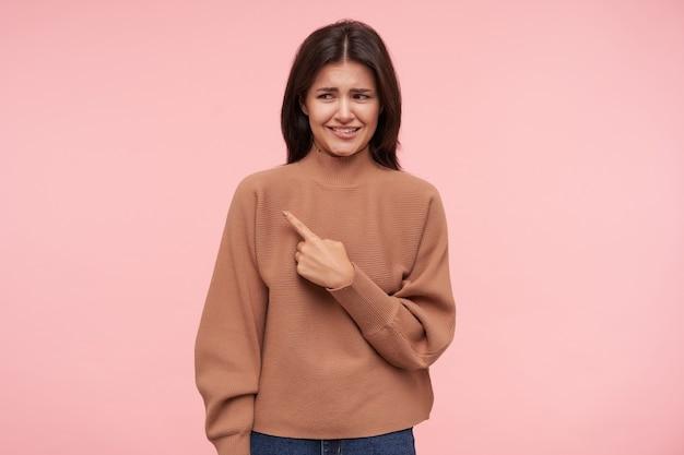 Foto de estúdio de uma jovem morena confusa fazendo uma careta ao apontar para o lado com o dedo indicador levantado, de pé sobre uma parede rosa com decote de polon.