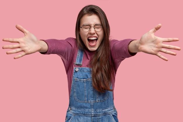 Foto de estúdio de uma jovem morena feliz dando um abraço, abrindo a boca e fechando os olhos de felicidade, usando um suéter roxo e um macacão jeans