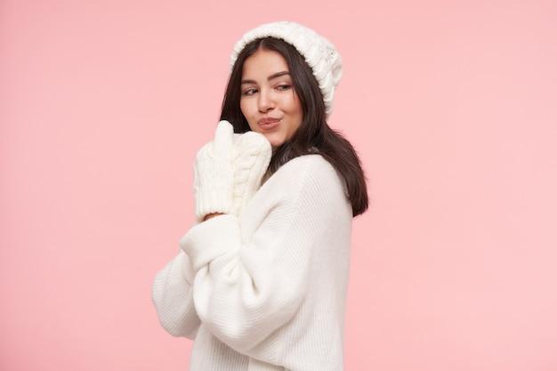 Foto de estúdio de uma jovem morena positiva vestida com roupas de malha branca, levantando as mãos com luvas no rosto e fazendo beicinho enquanto fica de pé sobre a parede rosa
