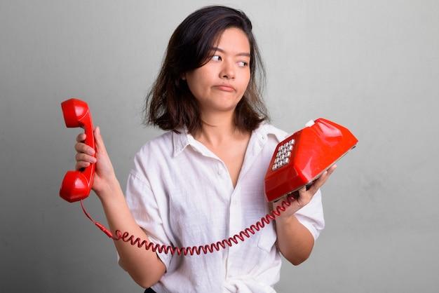 Foto de estúdio de uma jovem mulher asiática bonita com cabelo curto contra o branco