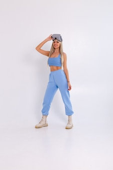 Foto de estúdio de uma jovem mulher atraente em um terno elegante azul quente usando óculos de realidade virtual em um branco