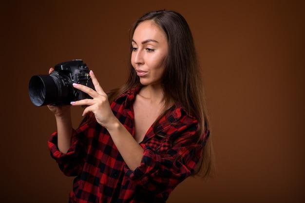 Foto de estúdio de uma jovem mulher bonita com uma câmera contra um fundo marrom