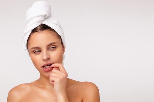 Foto de estúdio de uma jovem mulher de cabelo escuro semicerrando os olhos e mantendo o dedo indicador na parte inferior do lábio enquanto olha pensativamente para o lado, isolada sobre um fundo branco