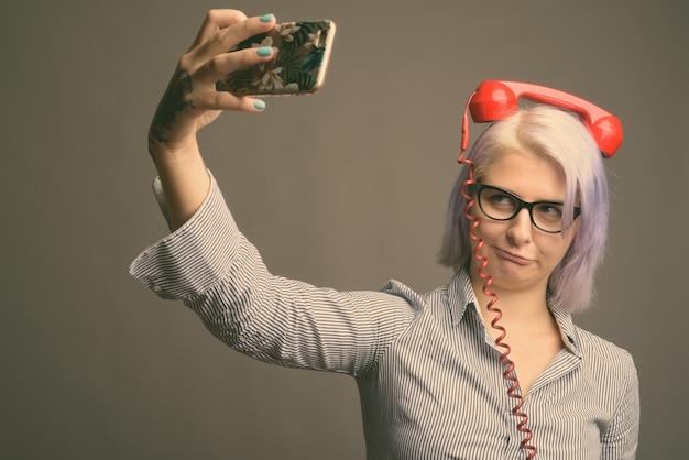 Foto de estúdio de uma jovem mulher de negócios bonita com cabelo curto colorido na cor cinza