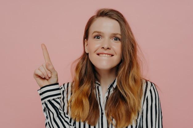 Foto de estúdio de uma jovem mulher emocional em roupas casuais, mordendo o lábio inferior e apontando para o espaço da cópia com o dedo indicador em pé, isolado em um fundo de cor, lembrando sobre a grande venda