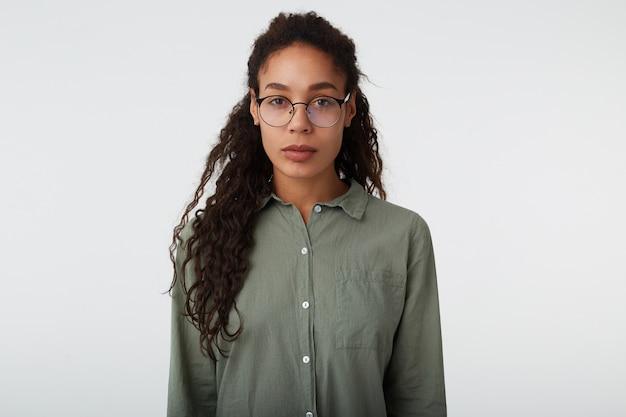 Foto de estúdio de uma jovem mulher encaracolada de olhos castanhos, cabelos compridos e pele escura, mantendo os lábios dobrados enquanto olha calmamente para a câmera, isolada sobre fundo branco