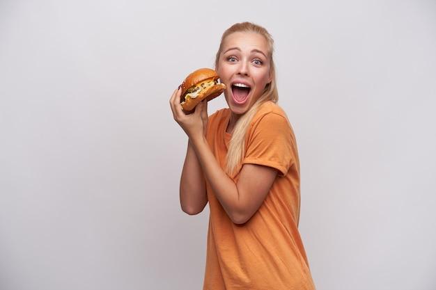 Foto de estúdio de uma jovem mulher loira animada de olhos azuis, vestida com uma camiseta laranja, segurando um grande hambúrguer nas mãos levantadas e olhando para a câmera com os olhos arregalados e a boca aberta, isolada sobre fundo branco