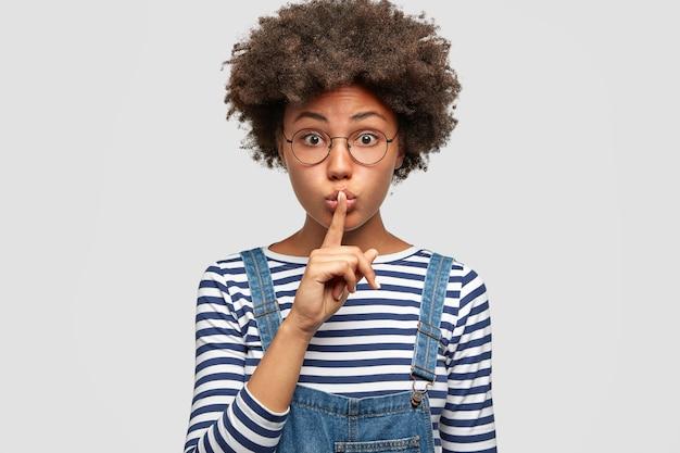 Foto de estúdio de uma jovem mulher misteriosa e agradável mostra um gesto silencioso