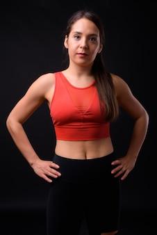 Foto de estúdio de uma jovem multiétnica linda mulher pronta para a academia contra um fundo preto