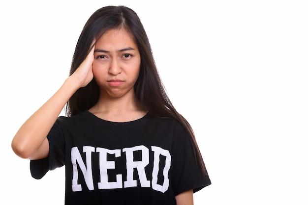 Foto de estúdio de uma jovem nerd adolescente asiática parecendo cansada