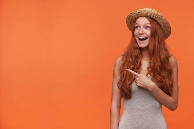 Foto de estúdio de uma jovem ruiva feliz com cabelo londrino, vestindo uma camisa cinza e chapéu de palha, posando sobre um fundo laranja com o dedo indicador levantado, olhando e apontando para o lado com uma cara surpresa