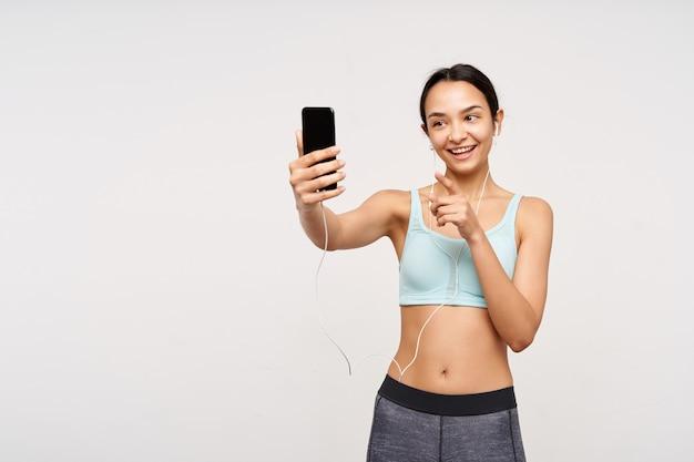 Foto de estúdio de uma jovem senhora de cabelos castanhos com penteado casual, de bom humor enquanto faz uma videochamada e aponta alegremente para a frente de seu telefone, isolada sobre uma parede branca