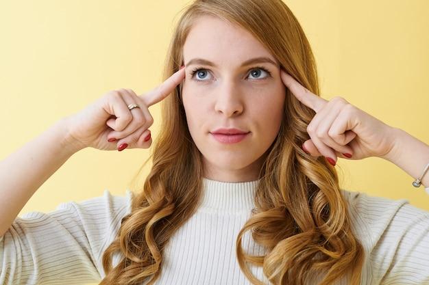 Foto de estúdio de uma jovem séria e pensativa, mantendo os dedos nas têmporas e olhando para cima com uma expressão pensativa, tentando se lembrar de algumas informações importantes ou pensando sobre uma decisão