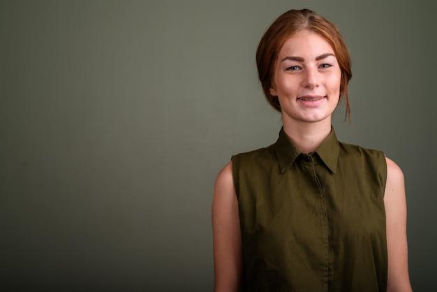 Foto de estúdio de uma jovem vestindo uma blusa sem mangas verde contra um fundo colorido