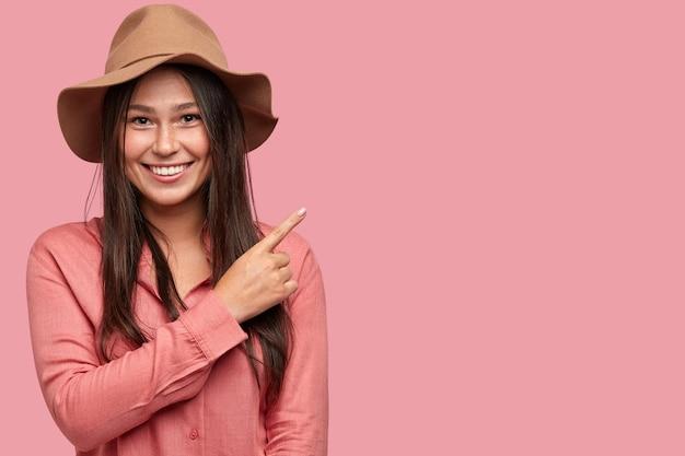 Foto de estúdio de uma linda garota sardenta com expressão alegre, indicada com o dedo indicador no canto superior direito