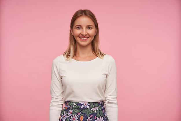 Foto de estúdio de uma linda jovem loira com penteado casual, olhando para a câmera com um largo sorriso alegre, em pé sobre um fundo rosa com blusa branca e saia florida com as mãos para baixo
