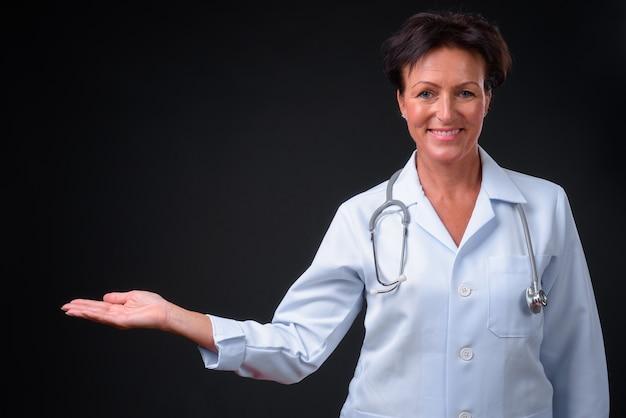 Foto de estúdio de uma linda médica escandinava madura com cabelo curto contra um fundo preto