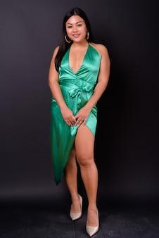 Foto de estúdio de uma linda mulher asiática com excesso de peso contra um fundo preto