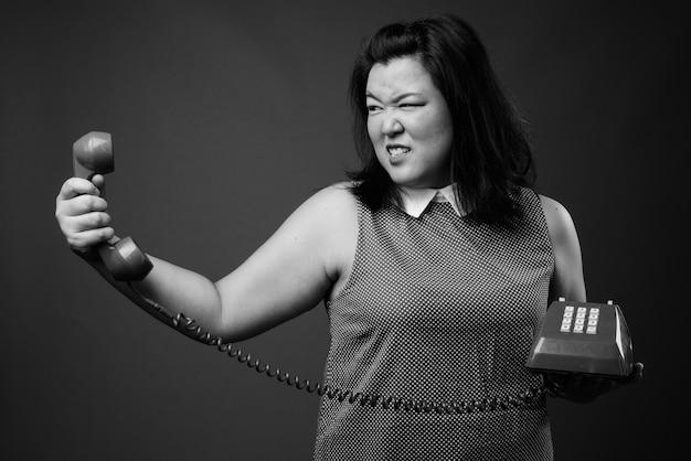 Foto de estúdio de uma linda mulher asiática com excesso de peso usando um vestido contra um fundo cinza em preto e branco
