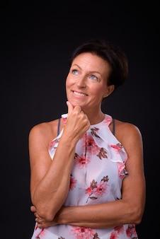 Foto de estúdio de uma linda mulher escandinava madura com cabelo curto contra um fundo preto