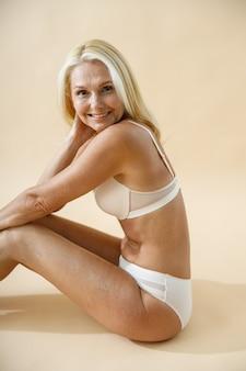 Foto de estúdio de uma linda mulher loira madura posando de cueca, sentada no chão e sorrindo para