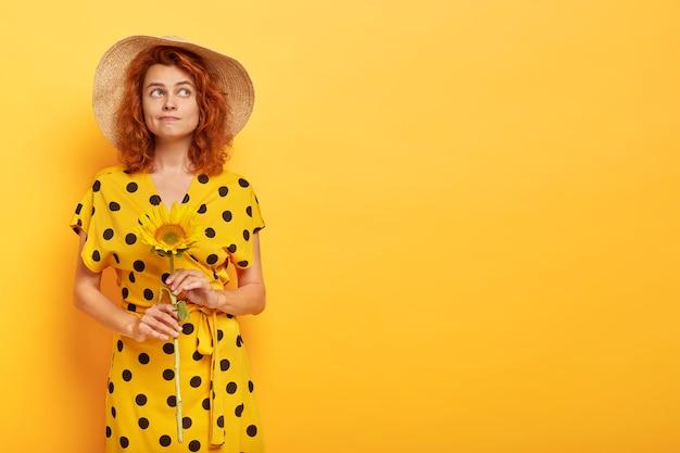 Foto de estúdio de uma linda ruiva posando em um vestido polca amarelo e chapéu de palha