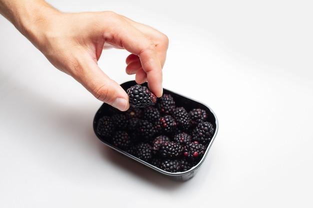 Foto de estúdio de uma mão masculina segurando um blackberry em uma caixa cheia de uns.