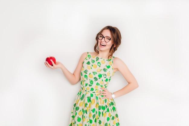 Foto de estúdio de uma menina morena sorridente, sorrindo amplamente. ela segura uma maçã vermelha na mão direita