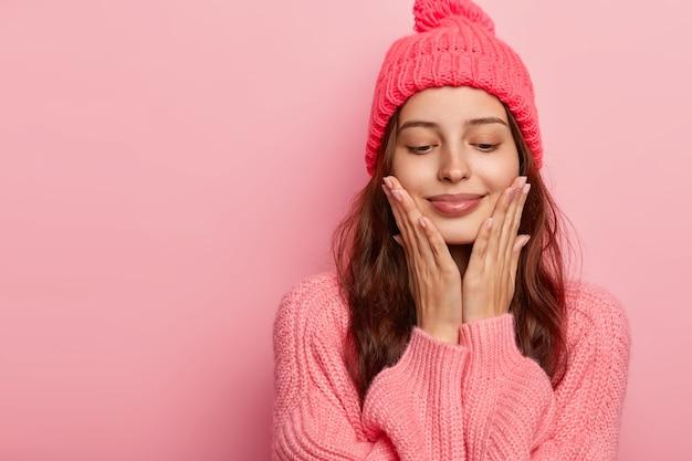Foto de estúdio de uma modelo feminina de aparência agradável tocando o queixo com as palmas das mãos, olhos fechados, cabelo escuro, vestida com roupa de inverno, isolada na parede rosa, espaço em branco